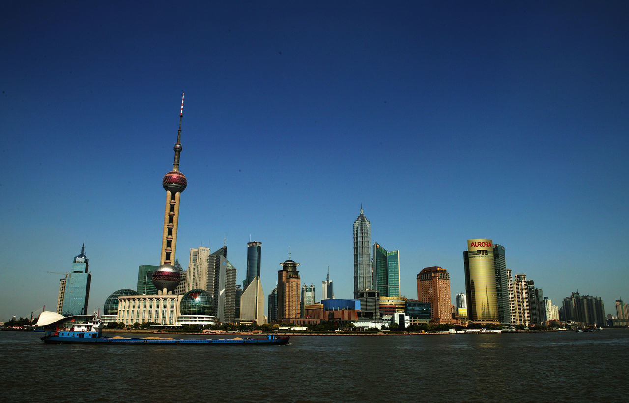 architecture, tall - high, built structure, building exterior, tower, skyscraper, city, clear sky, water, waterfront, blue, urban skyline, day, travel destinations, no people, modern, outdoors, tall, sky, nautical vessel, cityscape