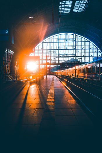 Train at railroad station platform during sunset