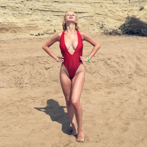 Full length of seductive young woman wearing swimsuit while standing at beach during summer