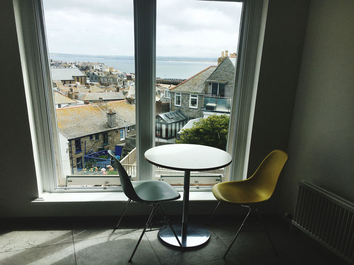 Empty chairs and table by window at home