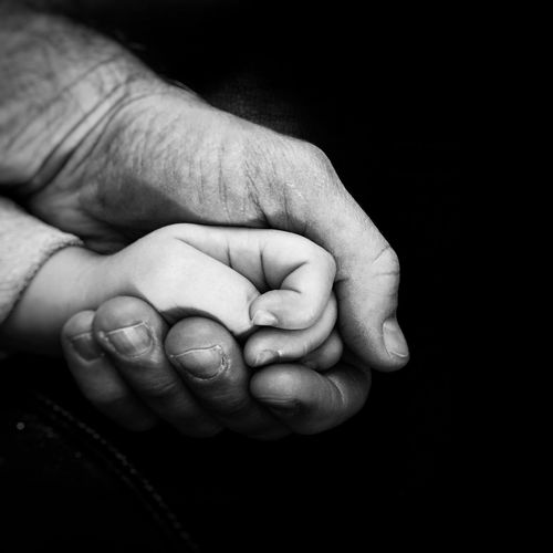 Cropped hands of man and baby against black background