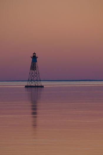 Tower at beach against clear sky at dusk