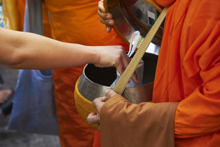 Cropped hand putting plastic bag in container held by monk