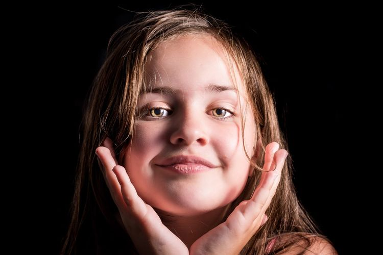 Close-Up Portrait Of Girl Smiling Against Black Background