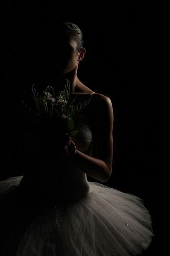 Ballet Dancer Holding Flowers Against Black Background