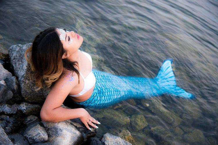 Woman Wearing Mermaid Costume While Resting In Sea
