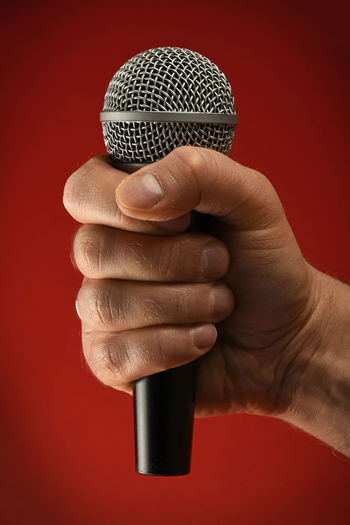 Cropped Hand Holding Microphone Against Red Background