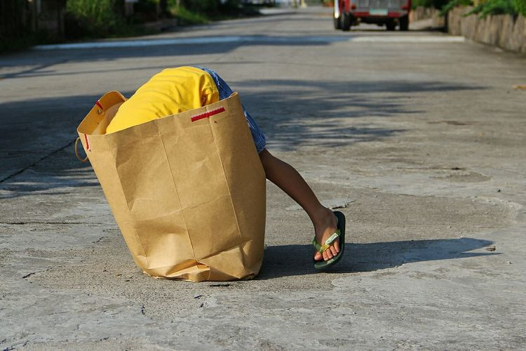 Boy Searching In Paper Bag On Street