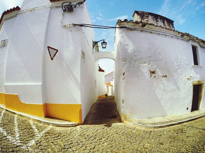 Street in the city of Portel, central Alentejo, 39 km from Evora, Portugal. Old Buildings Street Portel Alentejo Portugal Streetphotography Built Structure Architecture Day Nature Sunlight No People The Street Photographer - 2018 EyeEm Awards Entrance Door Building Exterior Communication Building Outdoors Text Wall - Building Feature Number Sky Old House Abandoned Western Script