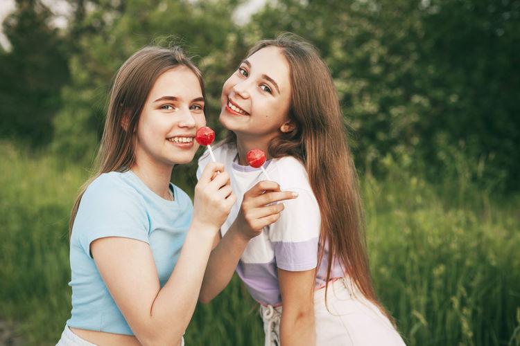 Portrait of smiling friends holding lollipops standing against plants in park