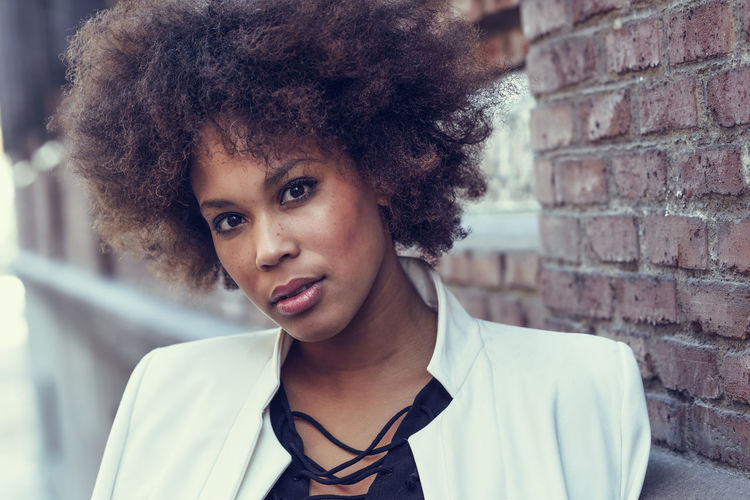 Close-up portrait of black woman with afro hairstyle standing in urban background. Mixed girl wearing white jacket and black dress posing near a brick wall The Fashion Photographer - 2018 EyeEm Awards Architecture Brick Brick Wall Casual Clothing Close-up Curly Hair Focus On Foreground Front View Hair Hairstyle Headshot Lifestyles Looking At Camera One Person Portrait Real People Wall Young Adult