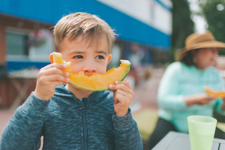Close-up of boy eating cantaloupe