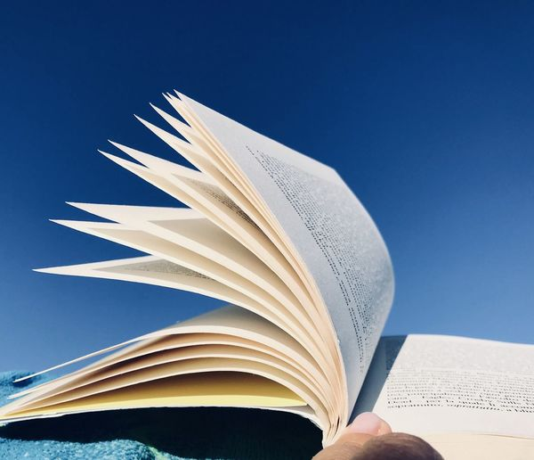 Close-up of hand holding book against blue sky