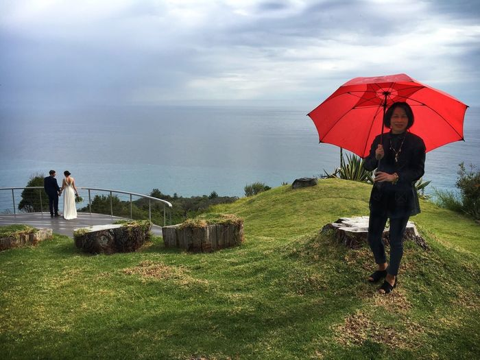 Big Sur Wedding Found On The Roll Wedding California Umbrella Rain Showers Vista Coastal Sky Cloudy Clouds Clouds And Sky Guest Bride And Groom Groom Bride Red Umbrella Woman Asian