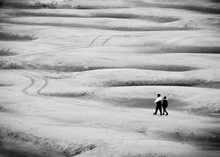 People walking on snow covered landscape