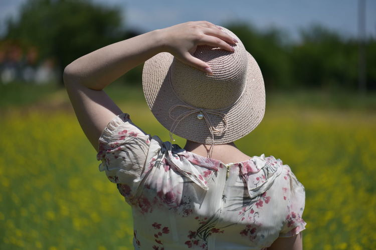 Midsection of woman wearing hat standing on field