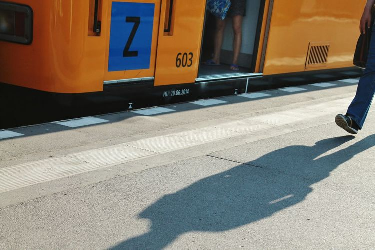 Low Section Of Man Walking By Yellow Train On Sunny Day