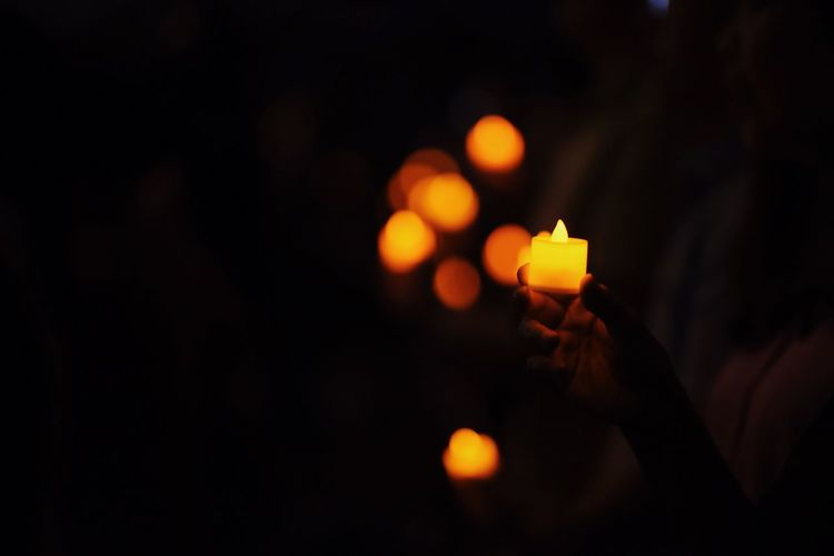 Close-up of hand holding illuminated candles against sky at night