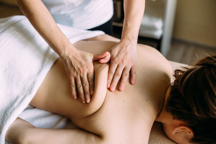 Massage therapist doing massage on the female body in the spa.