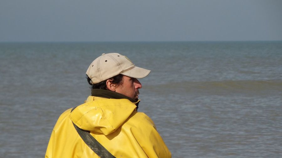 Rear view of man wearing cap against sea on sunny day