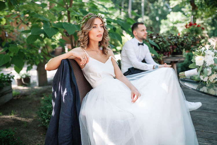 Thoughtful bride and bridegroom sitting on bench at park