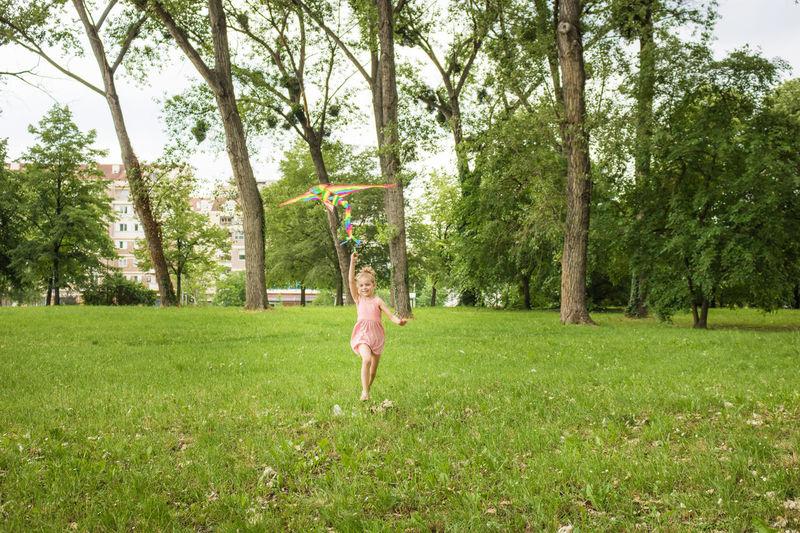 Full length of boy playing on grassy field