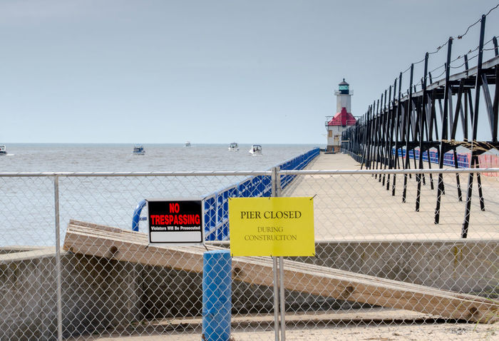 the St Joseph light house in Michigan USA undergoes a restoration project Lighthouse USA Beach Clear Sky Communication Danger Day Guidance Horizon Over Water Nature No People Outdoors Protection Restoration Project Safety Sea Sky St Joseph Michigan Text Warning Warning Sign Water