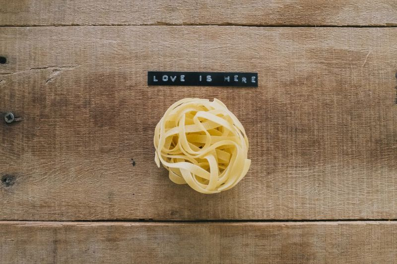 Close-up Directly Above Food Food And Drink High Angle View Indoors  Italian Food Love Mesage Message No People Pasta Raw Food Smiley Spaghetti Still Life Table Text Wellbeing Wood - Material Wood Grain Yellow