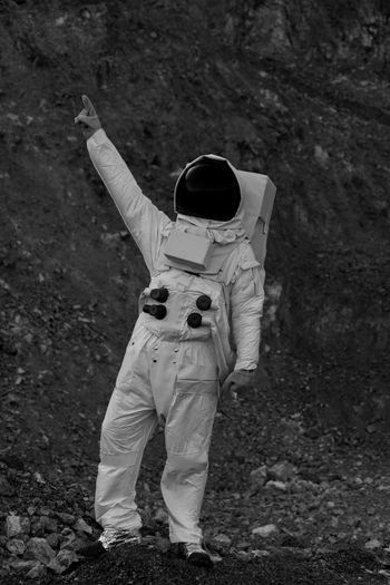 Full length of person in astronaut costume while pointing on field
