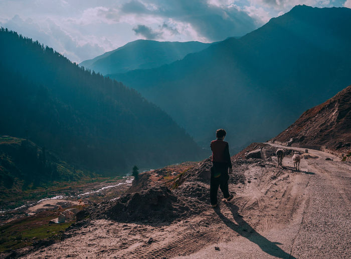 Rear view of man walking on mountain road against cloudy sky