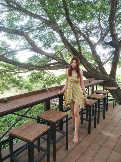Full length of smiling woman standing by chairs and tables against trees