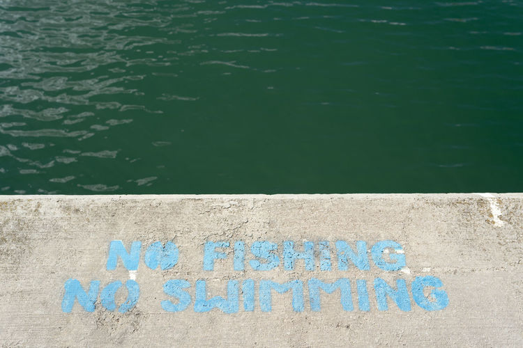 Text Western Script Communication Day No People Water Wall - Building Feature High Angle View Architecture Blue Sign Capital Letter Outdoors Wall Built Structure Message Graffiti Nature Information Turquoise Colored Gibraltar No Swimming No Fishing Minimal Minimalism