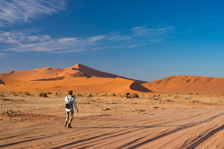 Rear view of hiker walking in namib desert against sky during sunny day