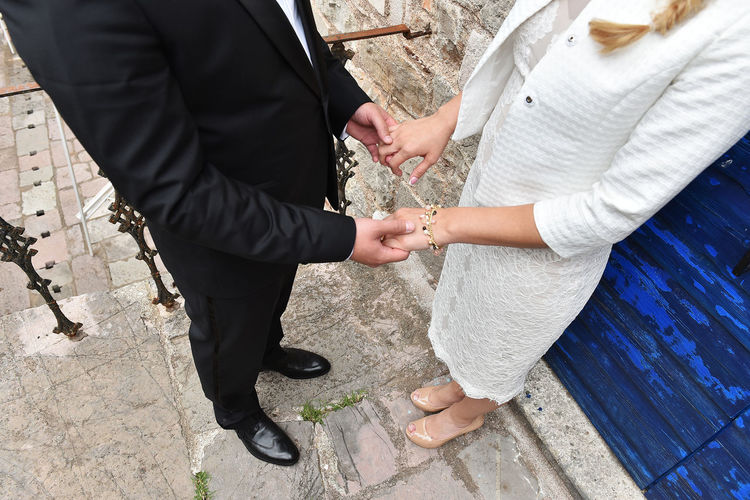 Low Section Of Wedding Couple Holding Hands
