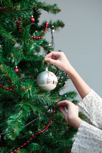 Decorating Christmas tree Ball Celebration Childhood Christmas Decorated Decorating Decoration Decorations Decorative Girl Holiday Home Joy Lifestyles Lights Ornament Pine Tradition Traditional Tree Tree Vertical Young