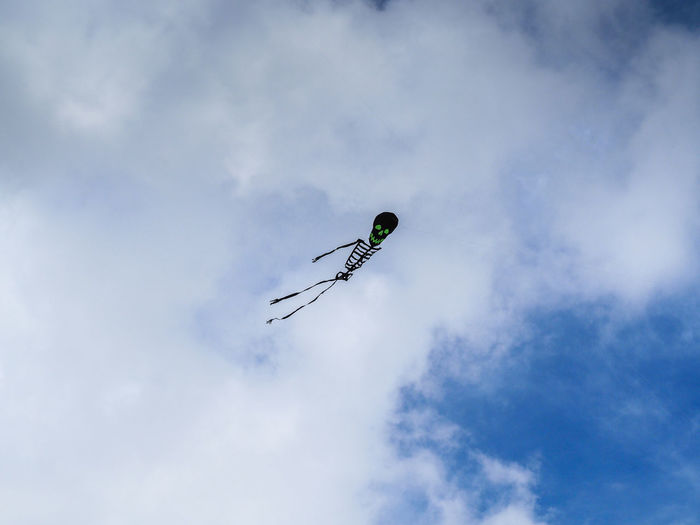 Low angle view of skeleton shaped kite flying in sky