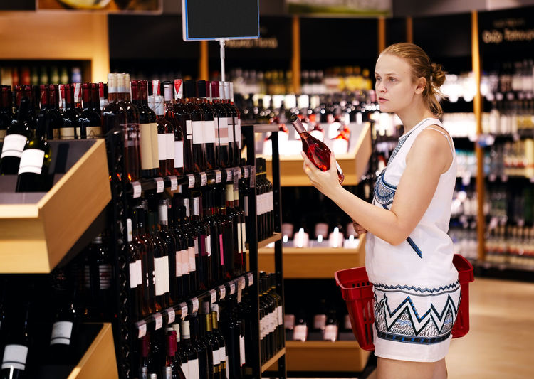 Side view of woman holding wine while standing at store