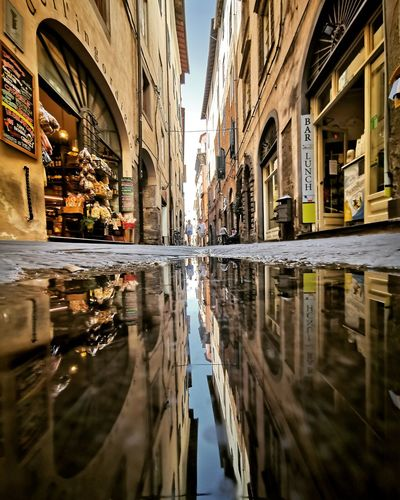 Reflection of buildings in puddle on street
