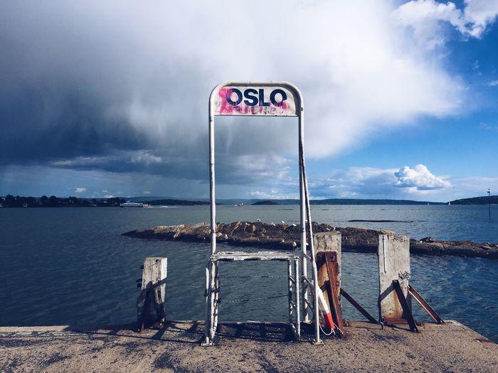 Information sign on beach against sky