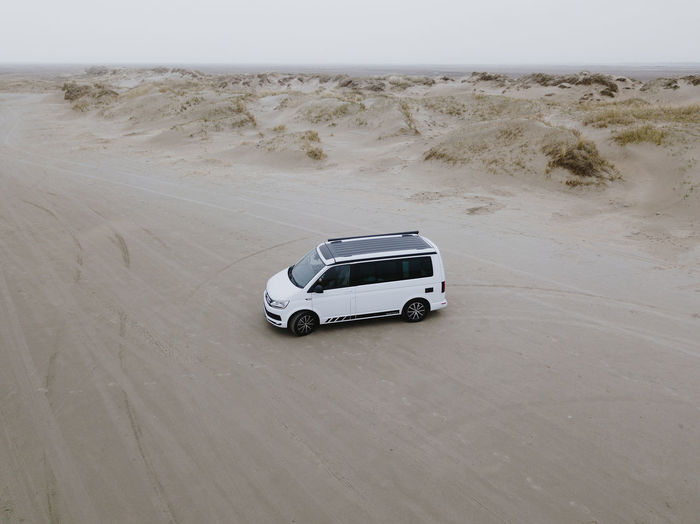 Arid Climate Car Climate Day Desert Environment High Angle View Land Land Vehicle Landscape Mode Of Transportation Motion Motor Vehicle Nature No People Off-road Vehicle Outdoors Road Sand Sand Dune Sports Utility Vehicle Transportation Travel
