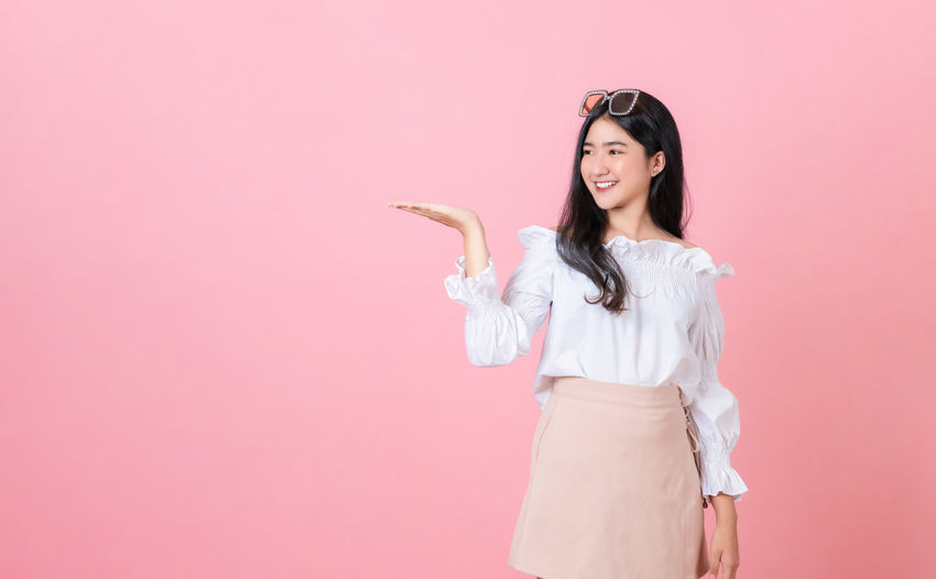 Full length of woman standing against pink background
