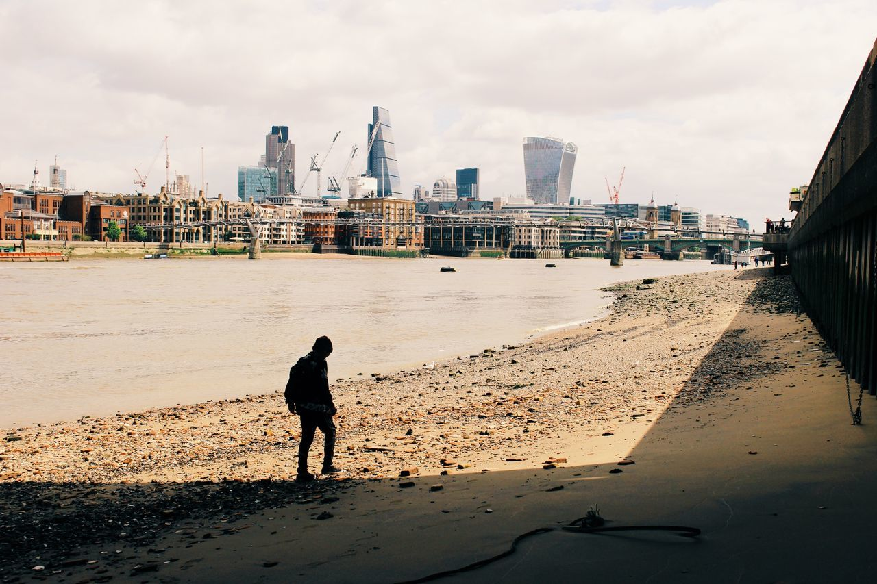 Silhouette man standing on thames riverbank against city