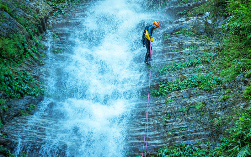 Full length of man climbing rock by waterfall