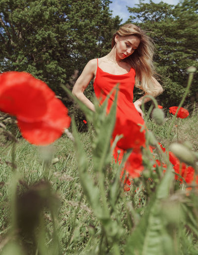 Young woman with red petals on field