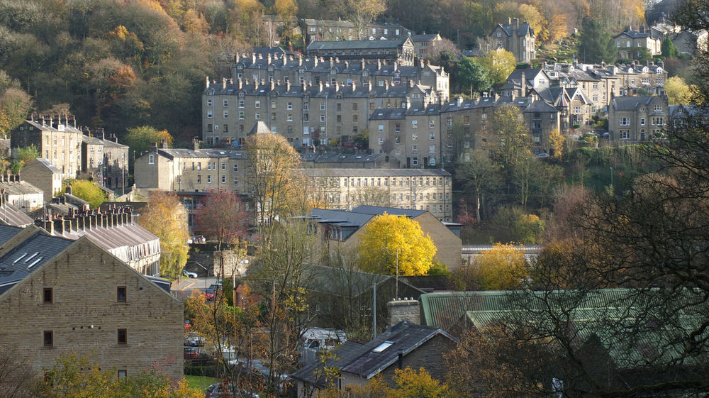 panoramic view of the town of hebden bridge in west yorkshire with streets of stone houses on steep hills in autumn sunlight surrounded by trees Hebden Bridge Architecture Built Structure Building Exterior Tree Building History Plant The Past Travel Destinations Nature City Day High Angle View No People Residential District Outdoors Travel Castle Tourism House Yorkshire