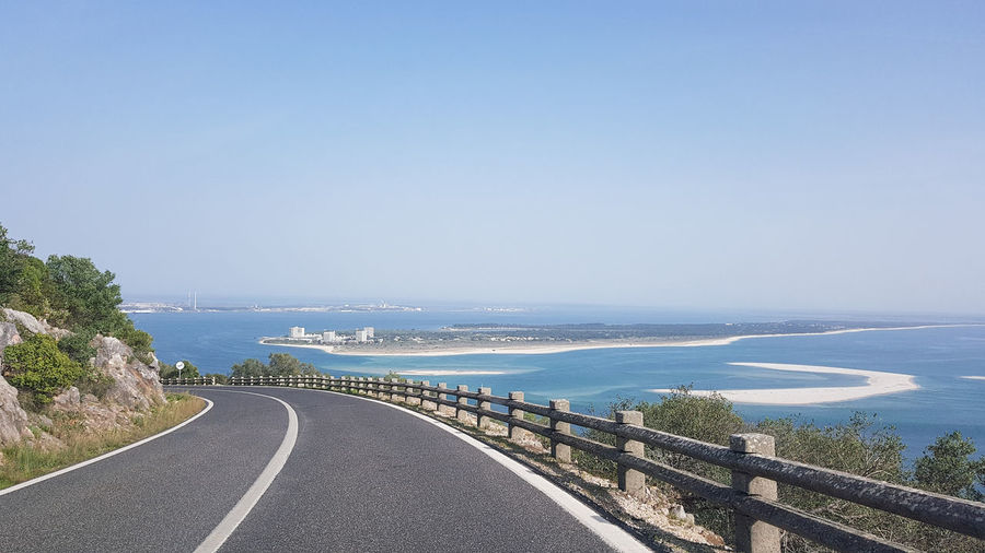 Panoramic view of road by sea against clear sky