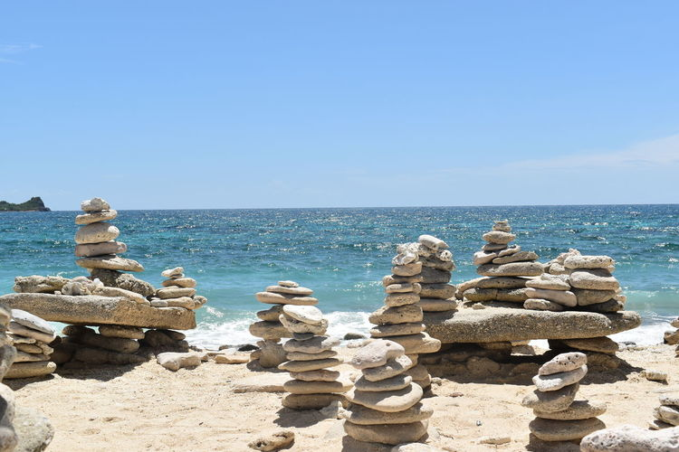 Stack of stones by sea against clear blue sky