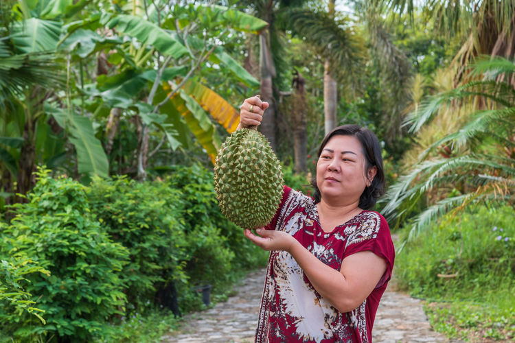 Mature woman holding durian while standing on footpath amidst plants