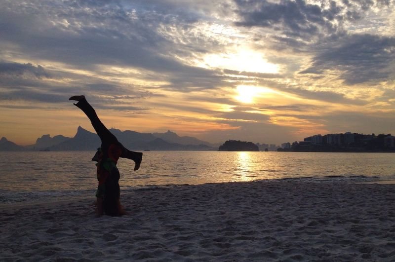 Person Doing Headstand At Beach During Sunset