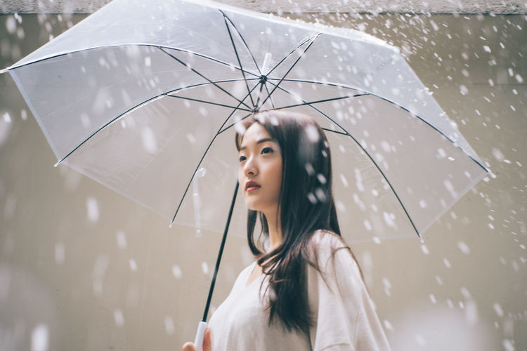Young Woman With Umbrella Looking Away